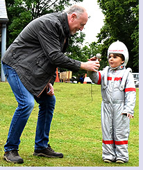 Richard Maryon passing microphone to spaceman Rory for official fete-opening